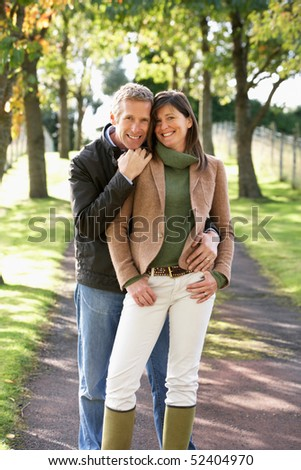 Portrait Of Romantic Couple Enjoying Outdoor Walk Through Autumn Park - stock photo