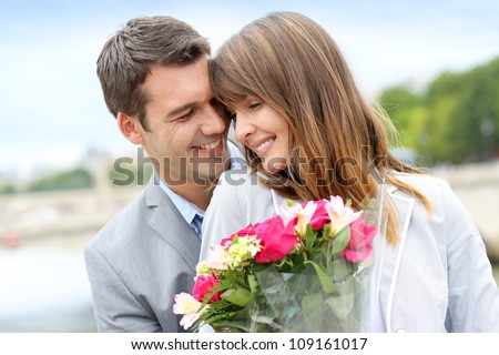 Portrait of romantic man giving flowers to woman - stock photo