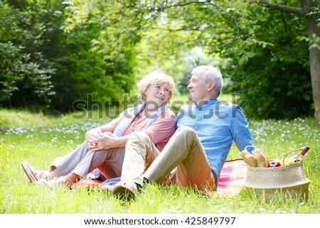 Portrait of romantic senior couple relaxing outdoor. - stock photo