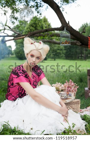 Portrait of romantic woman on a picnic in a fairy forest. - stock photo