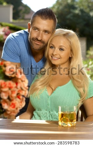 Portrait of romantic young couple sitting at summer garden, outdoors. Attractive, busty blonde woman with cleavage. - stock photo