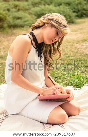 Portrait of romantic young woman writing in a diary sitting over the grass. Relax outdoor time concept. - stock photo