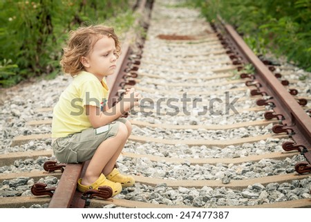 Portrait of sad blond little boy sitting on the rails at the day time - stock photo