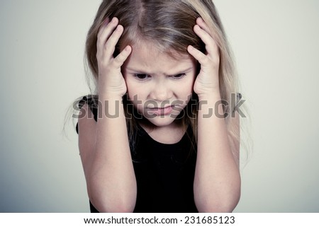 Portrait of sad blond little girl standing near wall and covers the face with hands - stock photo