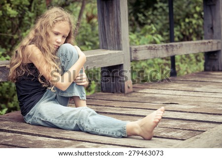 Portrait of sad blond teen girl sitting on the bridge at the day time - stock photo