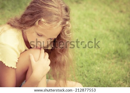 Portrait of sad blond teen girl sitting on the grass at the day time - stock photo