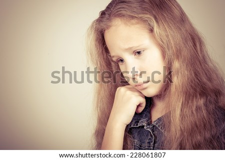 Portrait of sad blond teen girl standing near wall - stock photo