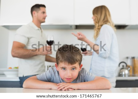 Portrait of sad boy leaning on table while parents arguing in background at home - stock photo