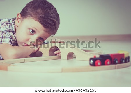 Portrait of sad little boy lying on floor at the day time. Concept of sad childhood. - stock photo