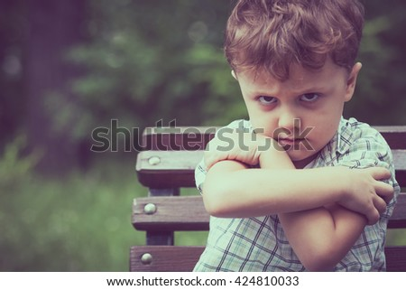 Portrait of sad  little boy sitting on bench at the day time. - stock photo