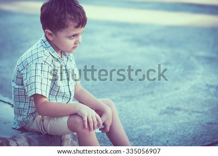 Portrait of sad little boy sitting on street at the day time - stock photo