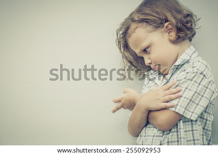 Portrait of sad little boy standing near the wall - stock photo