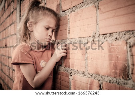 Portrait of sad little girl sitting near brick wall in the day time - stock photo