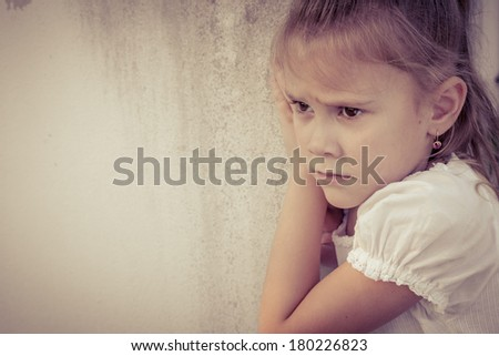 Portrait of sad little girl sitting near  wall in the day time - stock photo