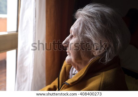 portrait of sad lonely pensive old senior woman looking in a window - stock photo