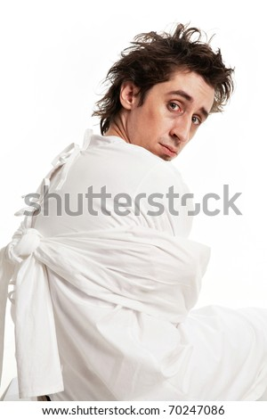 Portrait of sad mentally ill man in strait-jacket looking at camera - stock photo