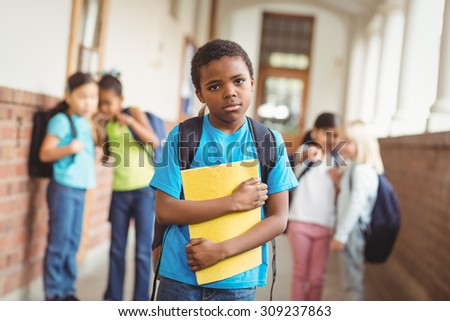 Portrait of sad pupil being bullied by classmates at corridor in school - stock photo