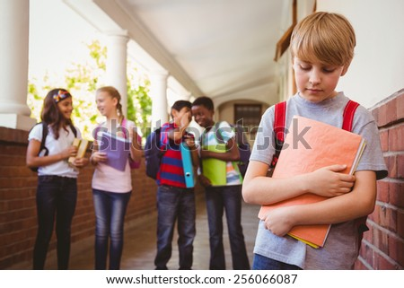 Portrait of sad schoolboy with friends in background at school corridor - stock photo