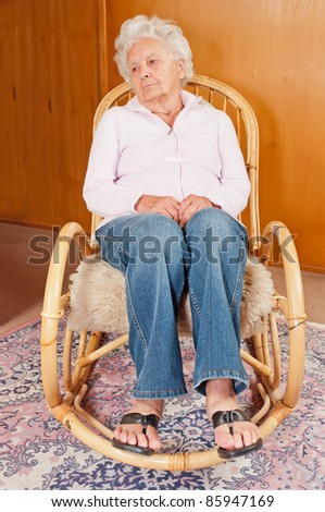 Portrait of sad senior woman in rocking chair. - stock photo