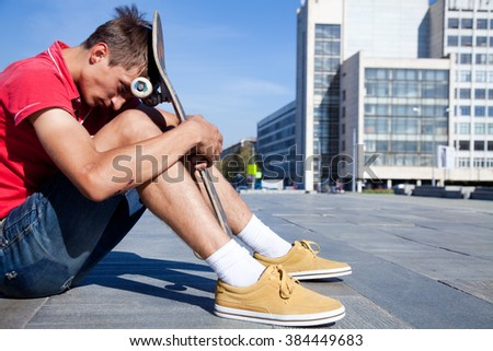 Portrait of sad skateboard on the street - stock photo
