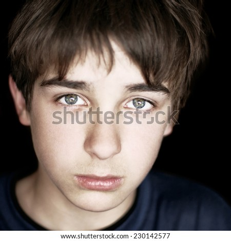 Portrait of Sad Teenager on the Dark Background closeup - stock photo