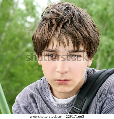 Portrait of Sad Teenager on the Summer Trees Background - stock photo