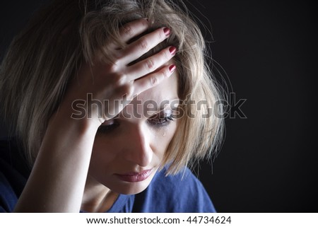 Portrait of sad woman crying, with her hand on the forehead and the tear on her cheek - stock photo