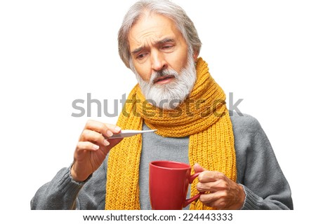 Portrait of sad worried caucasian ill senior man with gray beard and yellow scarf looking at a thermometer holding mug isolated on white background - stock photo
