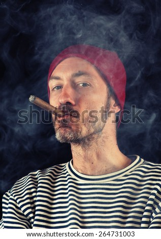 Portrait of sailor man smoking a cigar, shot over black background - stock photo