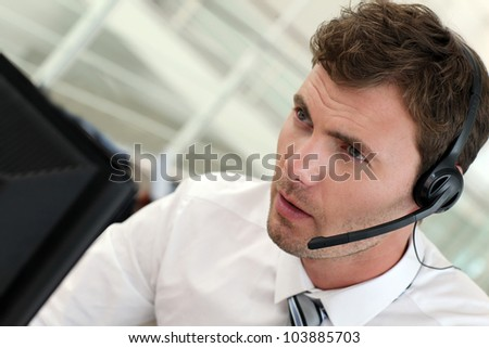 Portrait of salesman with headset on - stock photo