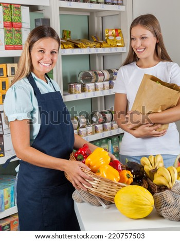 Portrait of saleswoman holding vegetable basket with female customer in supermarket - stock photo