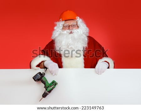Portrait of Santa Claus - builder in helmet builder holding the whiteboard over red background. Copy space. - stock photo