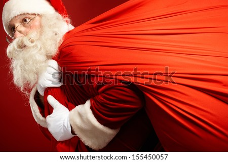 Portrait of Santa Claus carrying huge red sack with presents - stock photo