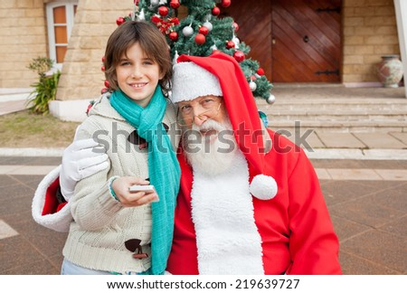 Portrait of Santa Claus embracing boy with smartphone outside house - stock photo