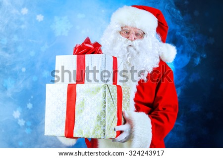 Portrait of Santa Claus holding gift boxes. Christmas time.  - stock photo
