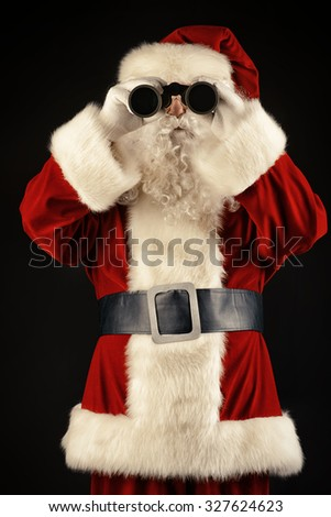 Portrait of Santa Claus looking through the binoculars over black background. Christmas time.  - stock photo
