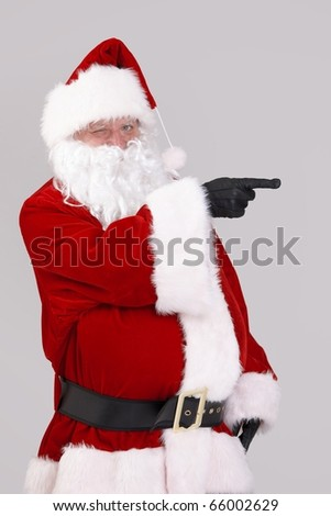 Portrait of Santa Claus pointing to blank space, looking at camera, isolated on gray background.? - stock photo