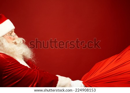 Portrait of Santa Claus pulling big red sack with gifts - stock photo