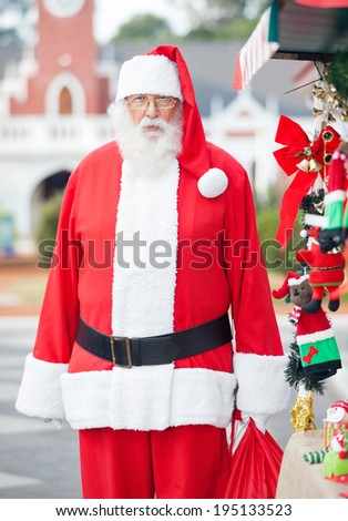 Portrait of Santa Claus standing in courtyard - stock photo
