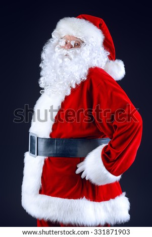 Portrait of Santa Claus standing sideways over black background. Christmas time.  - stock photo