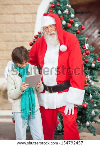 Portrait of Santa Claus standing with boy using digital tablet against Christmas tree - stock photo