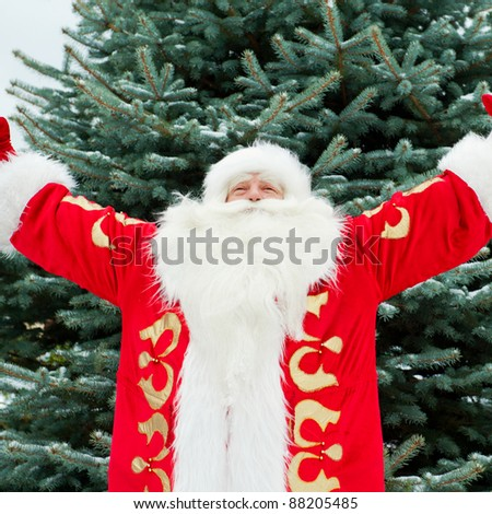 Portrait of Santa Claus standing with open hands outdoors at christmas tree. Snow falls. Natural light - stock photo