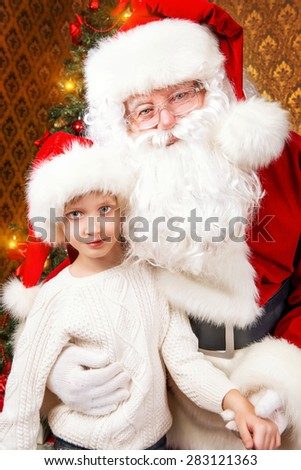 Portrait of Santa Claus with a boy sitting at home decorated for Christmas. Christmas scene.  - stock photo