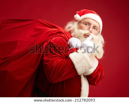 Portrait of Santa Claus with huge red sack keeping forefinger by his mouth - stock photo