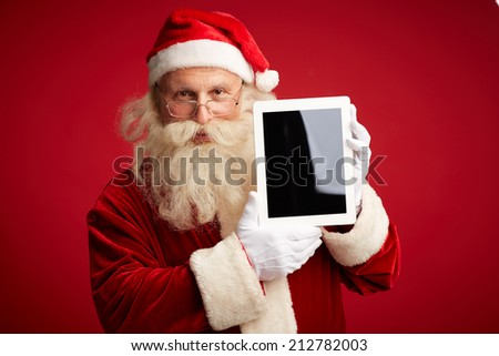 Portrait of Santa Claus with touchscreen looking at camera - stock photo