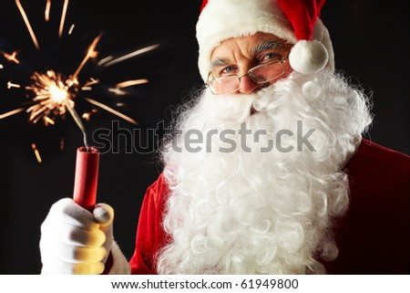Portrait of Santa with a sparkler isolated on black - stock photo