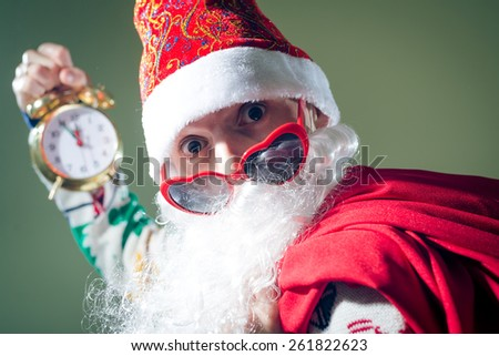 Portrait of Santa with heart shaped sunglasses holding clock showing five minutes to midnight  - stock photo