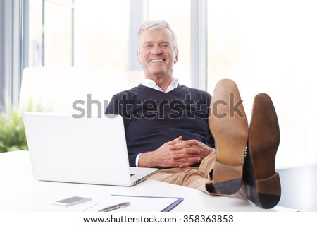Portrait of satisfied senior businessman sitting at workplace in front of computer and looking at camera while relaxing. Old professional man feet on office desk.  - stock photo