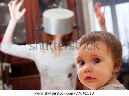 Portrait of scared baby against crazy mother with pan on head - stock photo
