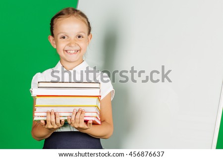 portrait of school girl in a school uniform near whiteboard with books . Learning, idea and school concept. Image on green background. - stock photo